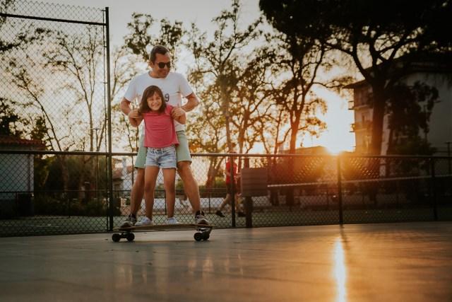 pere et fille font du skateboard au soleil couchant