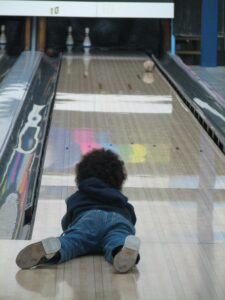 picture of kid bowling as free summer activities for kids