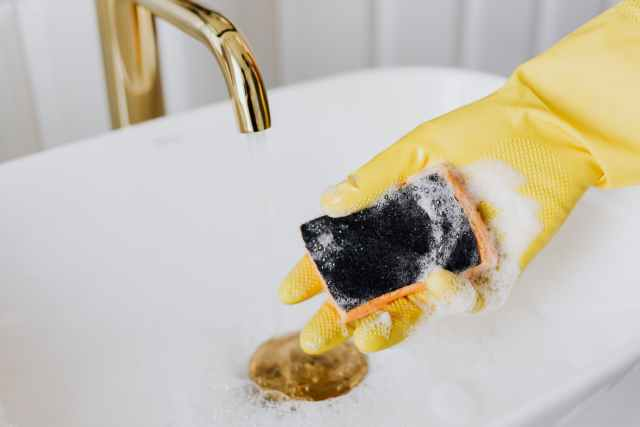 person in glove using detergent and sponge while cleaning sink