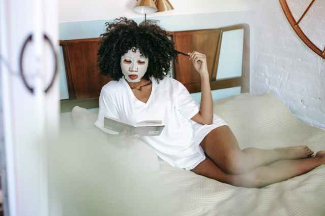 young black lady reading book on bed during skin care routine at home