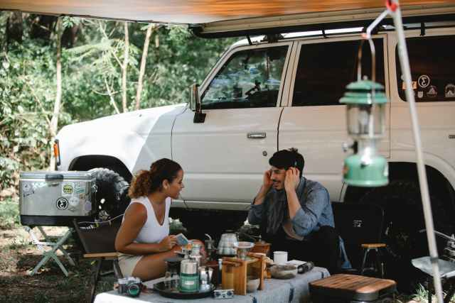 positive multiethnic friends sitting at table near van with awning in forest