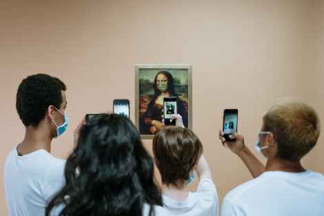 people taking picture of a painting of mona lisa with face mask | All 480,000 Works from The Louvre Have Gone Virtual