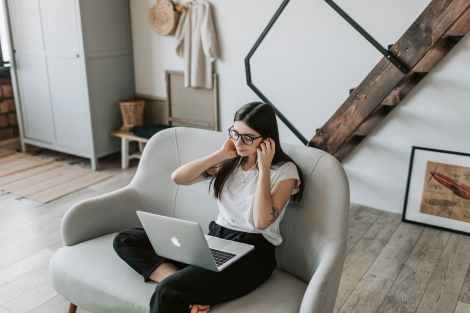 positive woman using earphones and laptop at home during free time