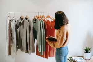 faceless female seller with notepad near clothes on hangers