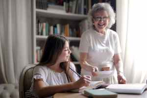 happy aged woman giving cookies and cup of hot drink to pleased granddaughter doing homework at home