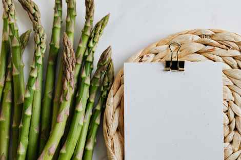 bunch of asparagus with blank paper sheet