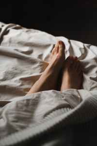 crop unrecognizable female feet lying in cozy bed
