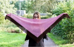 Woman holding an open crochet shawl
