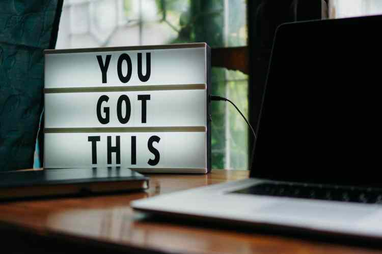 'You got this' sign sitting on desk next to computer and planner