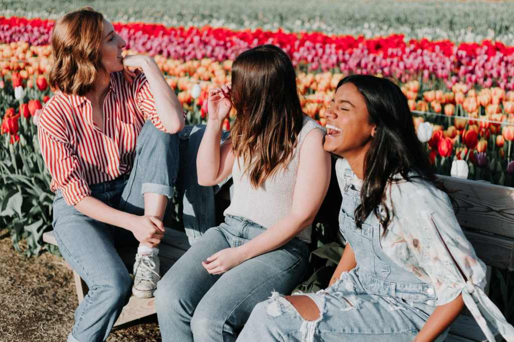 Relationships are better than phones - 3 young women sitting on a bench and laughing