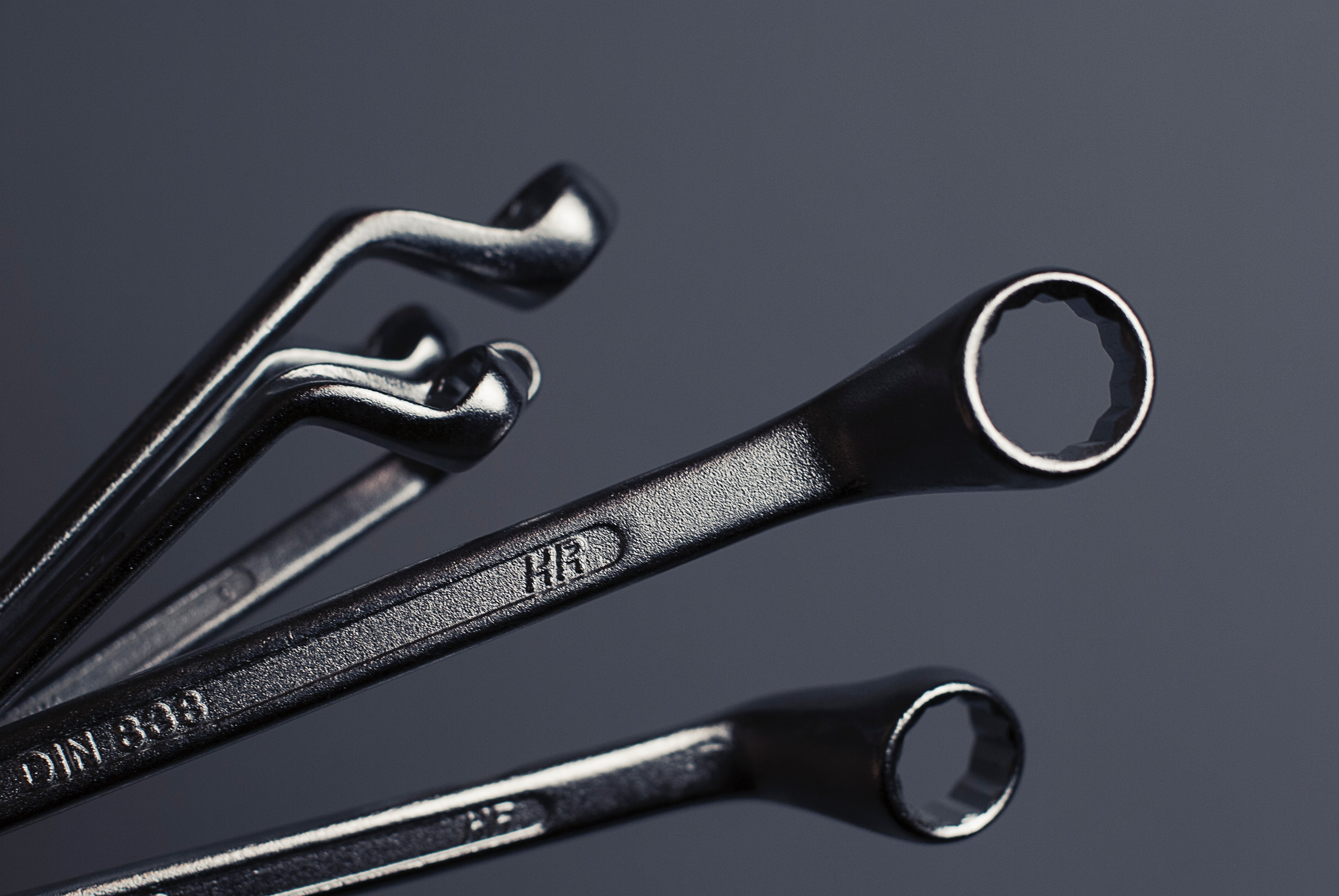 Multiple wrenches on a gray background.