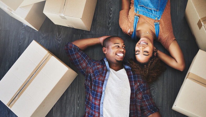 A young couple laying next to moving boxes getting ready to sell their house fast.