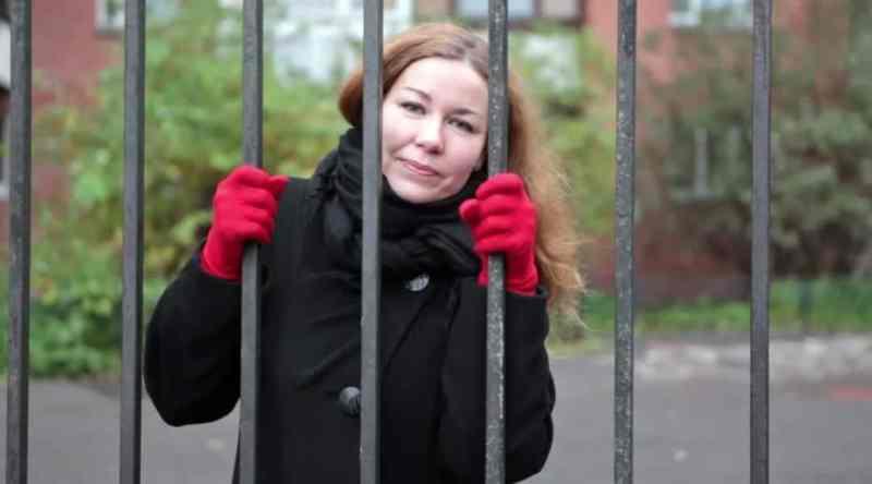 woman outside behind bars