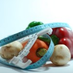 A selection of vegetables with a tape measure.