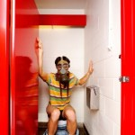 A man wearing a gas mask on the toilet.