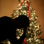 A shadow of a depressed man in front of a Christmas tree.