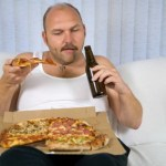 An overweight man drinking beer and eating pizza.
