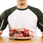 A man sitting down in front of a plate full of raw steak with a knife and fork.