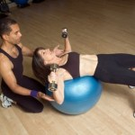 A woman doing dumbbell chest presses on a balance ball.