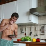 A man with toned abdominal muscles eating food in the kitchen.