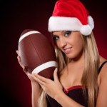 A woman with a Christmas hat holding a football.