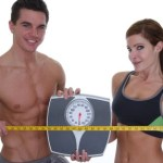 A healthy couple holding scales and a measuring tape.
