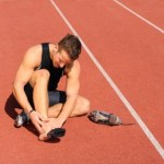 An injured runner sitting on a running track.