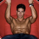 A man with toned abs sitting in a red chair.