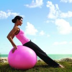 A woman on a pink exercise ball in an empty field.
