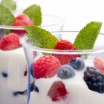 Two clear glasses of yogurt and fruit.