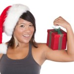 A fit girl in a Christmas hat flexing her arm whilst balancing a present.