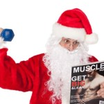 Santa lifting a dumbbell and reading a muscle building magazine.