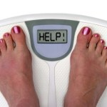 Two feet on a set of weighing scales with the message help.