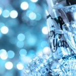 "A blue tinted bottle of champagne that reads ""Happy New Year""."