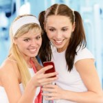 2 women in a gym looking at a mobile phone.