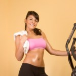 A sweaty girl standing on an elliptical machine with a towel.