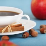 A cup of coffee an apple and some hazelnuts.