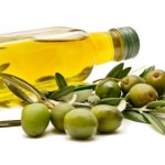 A bottle of olive oil on it's side next to a branch of green olives.