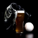 A black baseball glove on top of a pint of beer with a white baseball to the right.