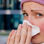 A woman with a cold blowing her nose.
