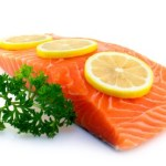 A piece of raw salmon garnished with lemon and parsley.