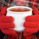 A woman with gloves holding a bowl of hot tomato soup.