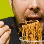 A man eating lots of noodles.