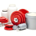 A collection of sports supplements next to a set of red dumbbells.