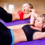 Two women doing sit ups.