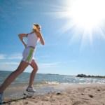 A woman running on a sunny beach.