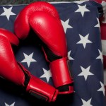 An American flag next to a pair of boxing gloves.