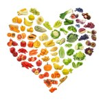 A selection of fruits and vegetables arranged in a heart shape.