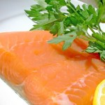 A close up shot of a salmon fillet garnished with lemon and parsley.