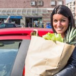 A woman standing next to a car with a bag of groceries.